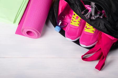Op een houten vloer wordt een sporttas met roze spullen geopend Stockfoto