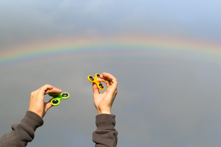 Two spinners in the hands on the background of the rainbow Stock Photo