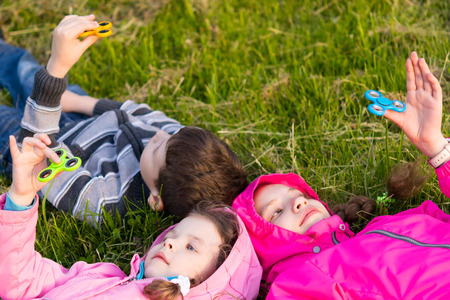 Children lie on the grass and play in the spinner