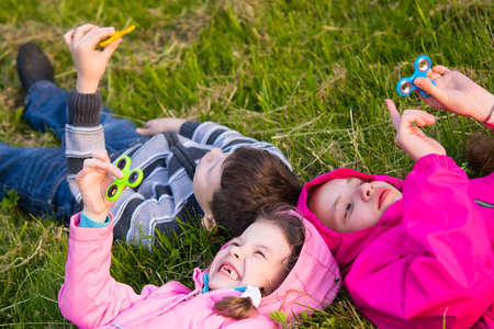 Children lie on grass smiling and playing in spinner