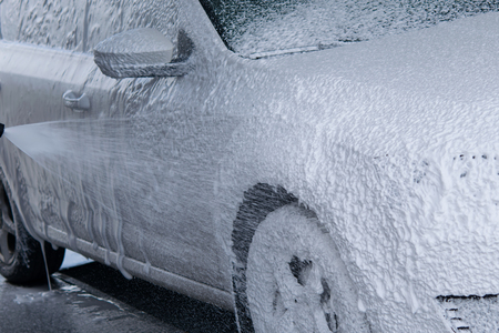 Contactless foam for washing the car flows down the body of the car