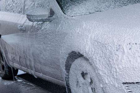 La espuma sin contacto para lavar el automóvil fluye por el cuerpo del automóvil. Foto de archivo - 83402916