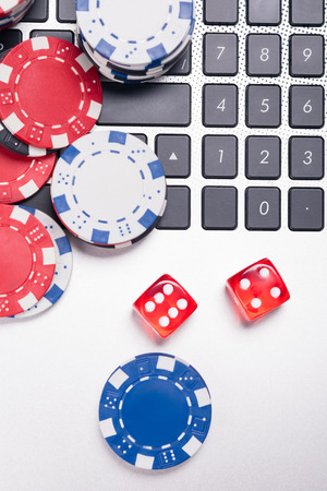 Cash chips and cubes, folding on a laptop, playing poker on the Internet