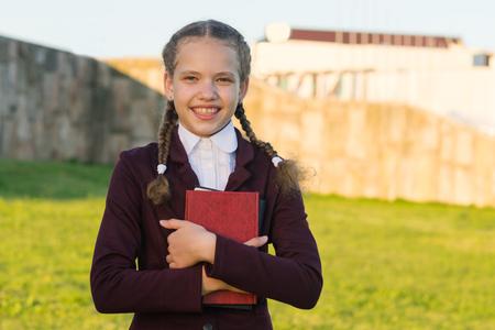 Meisje in schooluniform met een map in haar handen