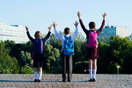Tři školáci přátelsky chodí v parku a zvedají ruce nahoru Reklamní fotografie
