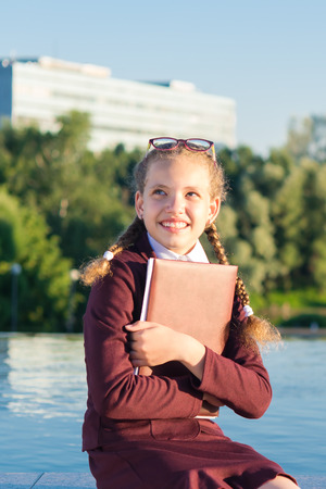 girl in school uniform holds a folder for school Stock Photo