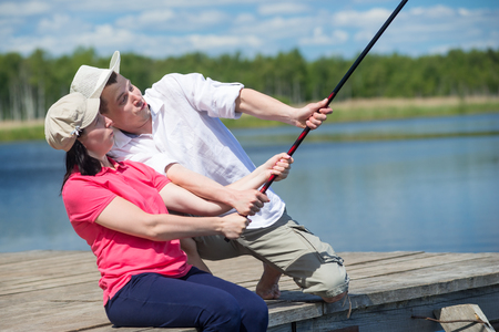 looking for love: man helps a woman catch a fish from a pier on the river