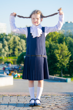 Little girl schoolgirl, took up pigtails with her hands Stock Photo