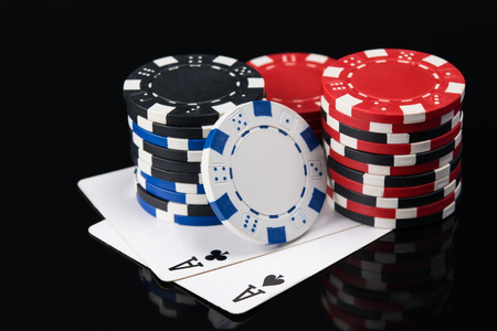 two large playing cards with poker chips on a dark background Stock Photo