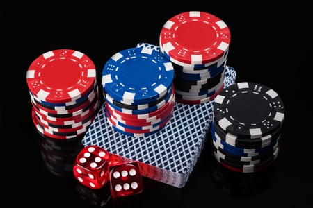 beautiful dice set, cards and poker chips on a black background