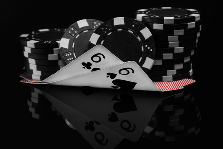 two small cards in poker under the poker chips reflected on black background Stock Photo