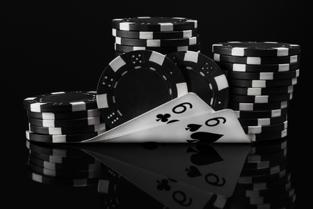black white idea of poker chips and poker cards in poker on a black background Stock Photo