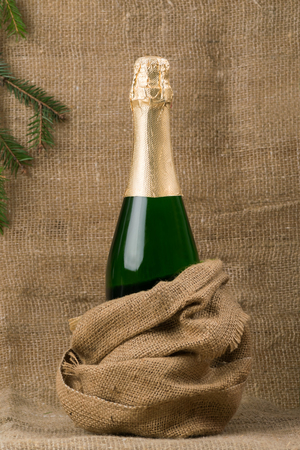 closed bottle of champagne wine, against a background of coarse, brown fabric