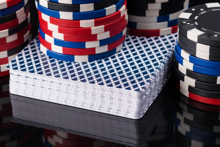 deck of poker cards on a black background with poker chips