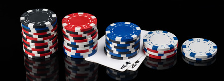 chips and poker cards lie in length on a black background with reflection