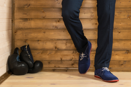 boxing gloves lie on the floor next to a man, against the background of a wooden wall Stock Photo