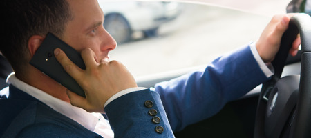 a man in a car talking on the phone with an insurance company