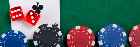 set of multi-colored playing chips, on green cloth and cards Stock Photo
