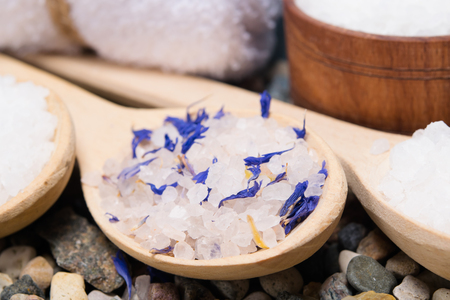 background with sea salt with elements of a blue flower, in a wooden spoon Stock Photo