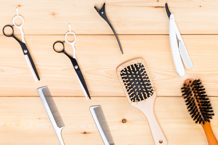 combs and scissors for fashionable haircuts on a light wooden background