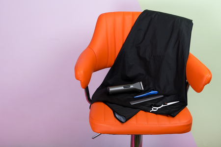 hairdressers set for shaving hair, on an orange chair, there is a place for an inscription Stock Photo