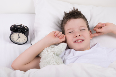 the boy on the bed closes his ears from the alarm bell