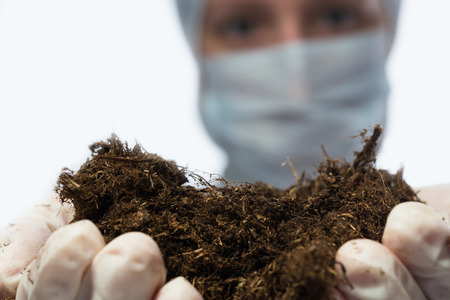 laboratory assistant woman holding soil in front of her Stock Photo