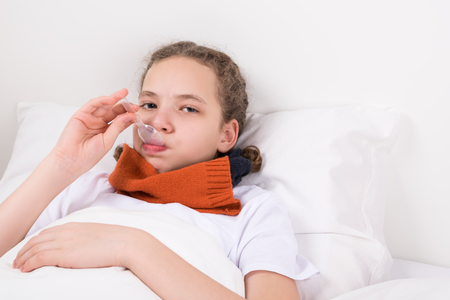 girl on the bed taking medicine for sore throat