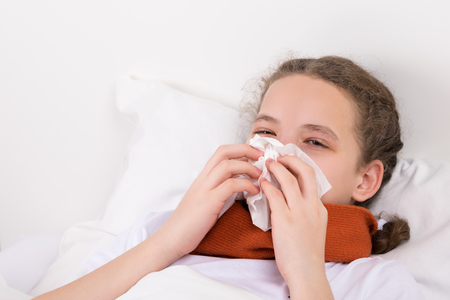 girl in bed blows a snot from her nose into a napkin Stock Photo