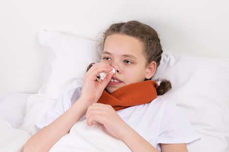 girl in bed warms her throat with a scarf and wipes her nose with a napkin Stock Photo