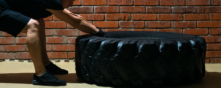 crossfit occupation with an automobile tire, against a brick wall background