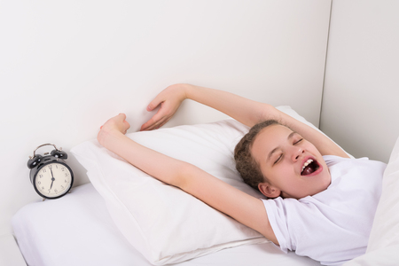 girl teenager with prosone pulls her arms up, in bed next to the alarm clock