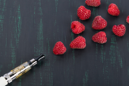 Electronic cigarette and a form of smoke from raspberries on a black board