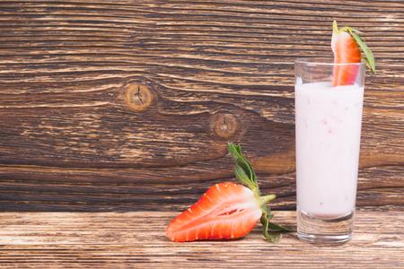 sur un fond en bois sombre, yaourt et fraises fraîches tranchées