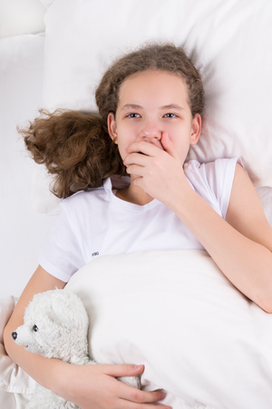 girl yawns in bed and hugs a toy polar bear