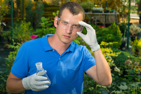 A man investigates liquid fertilizer for plants in the greenhouse