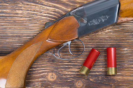 Two red cartridges on a dark wooden board, and a hunting rifle Stock Photo