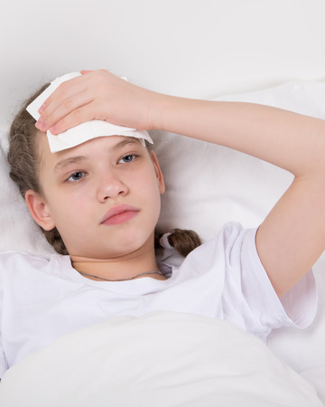 the girl lies on the pillow and holds on to the sick head