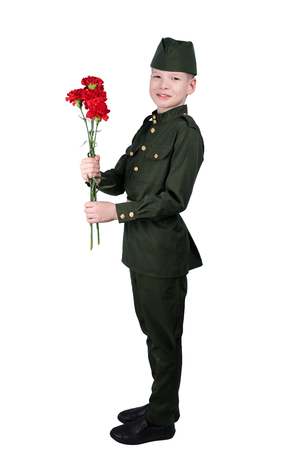 boy in military uniform holds a bouquet of red flowers in his hand, isolated on a white background in full length Stock Photo