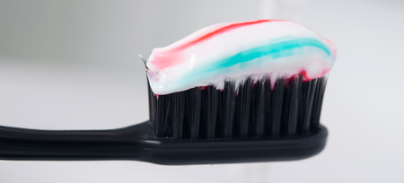 black toothbrush with paste on it, on a light background of a shell Stock Photo
