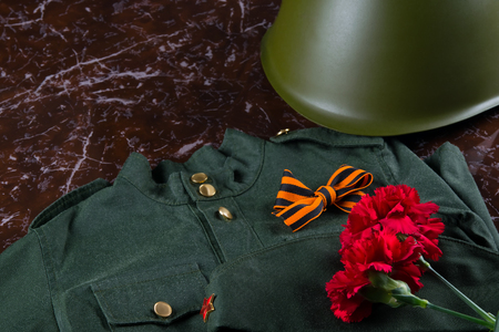 red carnations on marble and uniform with a St. George ribbon and helmet, as the background by May 9 Stock Photo