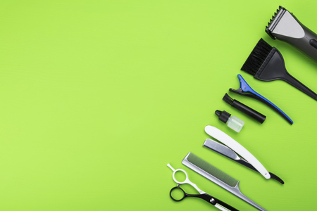 set for cutting hair from 8 objects lies in a corner on a green background
