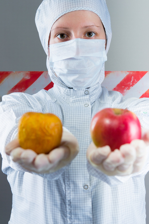 scientist in white protective suit, holds 2 apples, fresh and infected
