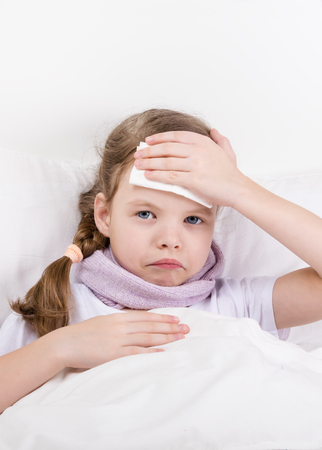 a little girl with a sore throat lies in bed and applies a compress to the sore head