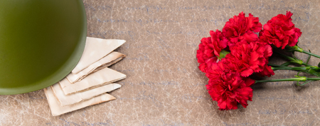 carnations, military helmet and old letters on a texture background with an inscription
