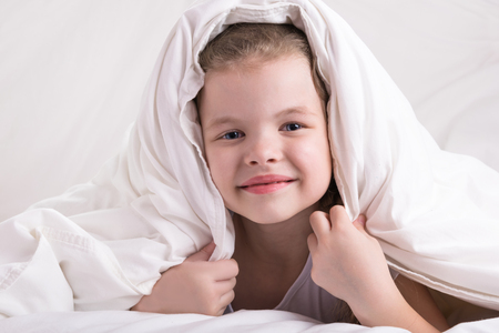 the girl hid her head under a white blanket, looked and smiled, close-up Reklamní fotografie