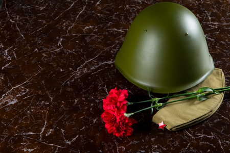 military helmet, carnations and a pilots cap, against the background of the monument Stock fotó