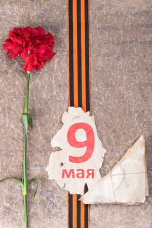 red flower and inscription on May 9, lie on an old paper