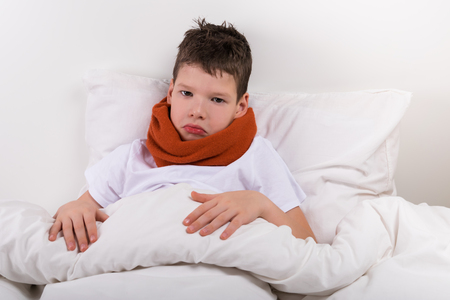 sad boy lies on the bed, neck is rewound with a warm scarf Stock Photo