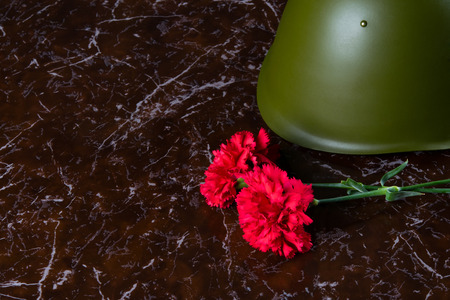 military helmet and carnations, against the background of the monument